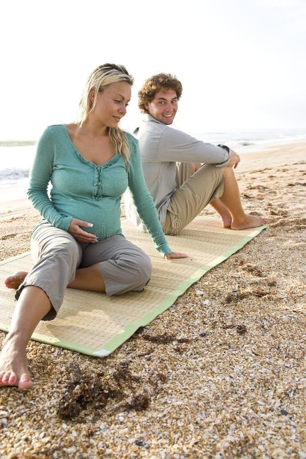 Jonge zwangere paarzitting op mat bij strand royalty-vrije stock foto