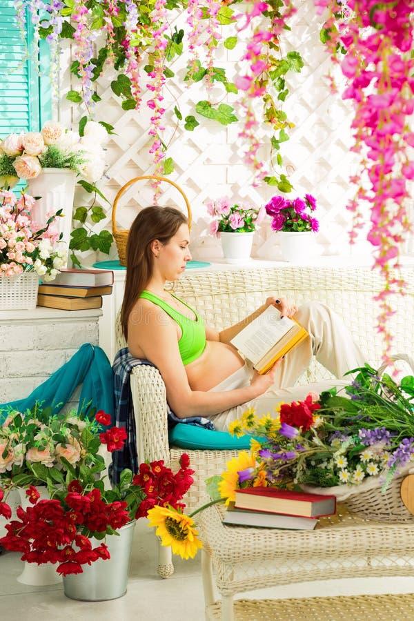 Jonge zwangere vrouw die een boek in een de zomerterras lezen stock fotografie