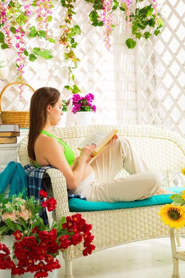 Jonge zwangere vrouw die een boek in een de zomerterras lezen stock foto's