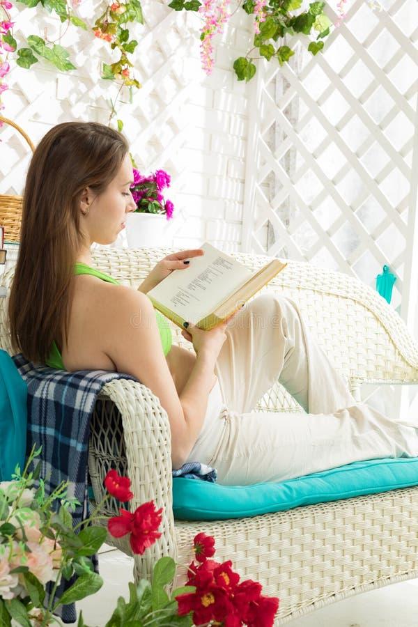 Jonge zwangere vrouw die een boek in een de zomerterras lezen royalty-vrije stock afbeeldingen