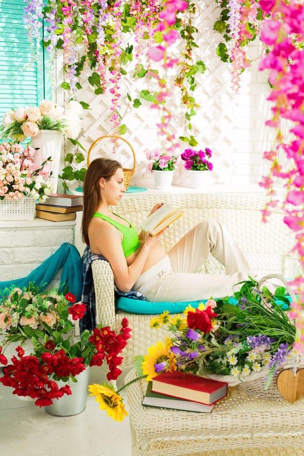 Jonge zwangere vrouw die een boek in een de zomerterras lezen stock afbeeldingen