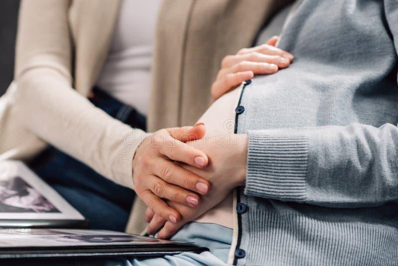Jonge zwangere vrouw die fotoalbum bekijken met moeder op grijze bank stock foto