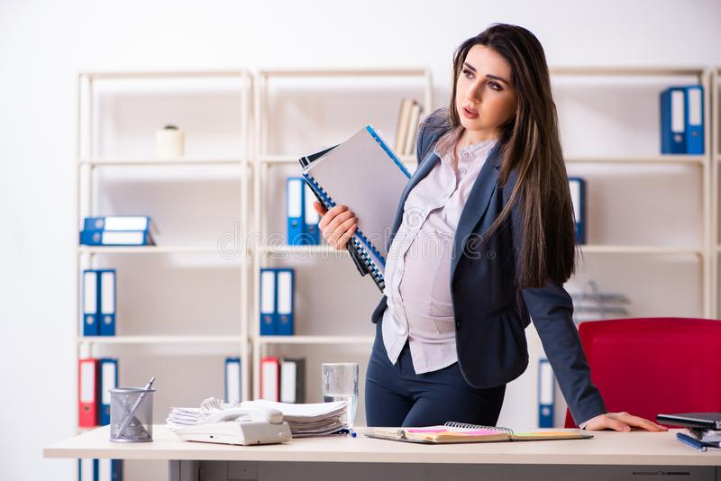 Jonge zwangere vrouw die in het bureau werken stock fotografie