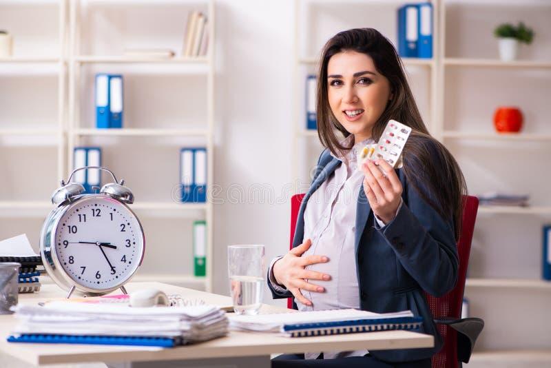 Jonge zwangere vrouw die in het bureau werken stock afbeeldingen