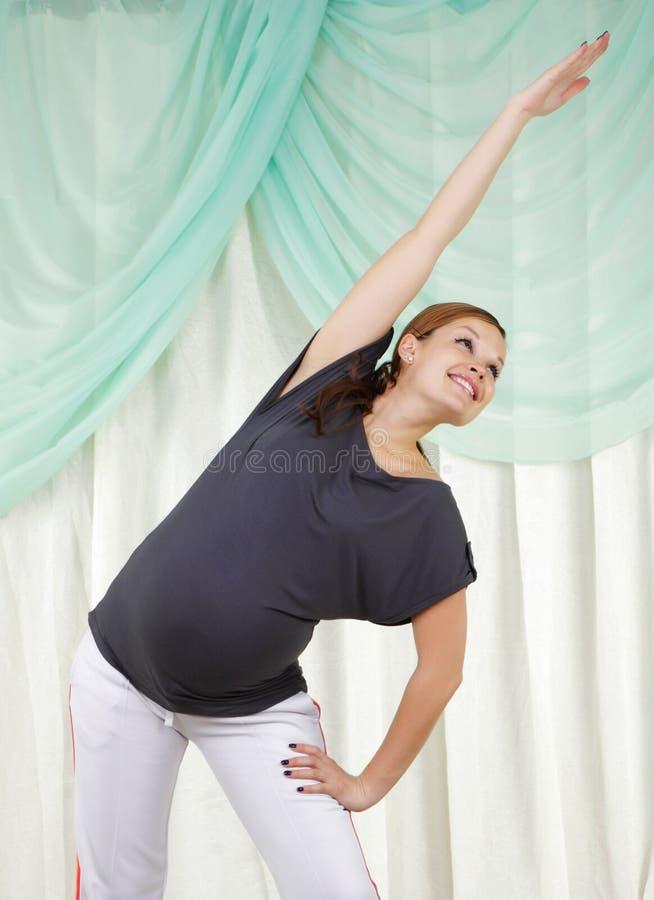 Jonge zwangere vrouw die oefeningen doet royalty-vrije stock afbeeldingen