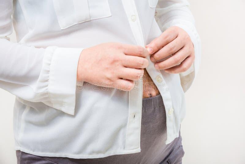 Jonge zwangere vrouw die probeert om de blouse omhoog dicht te knopen stock foto