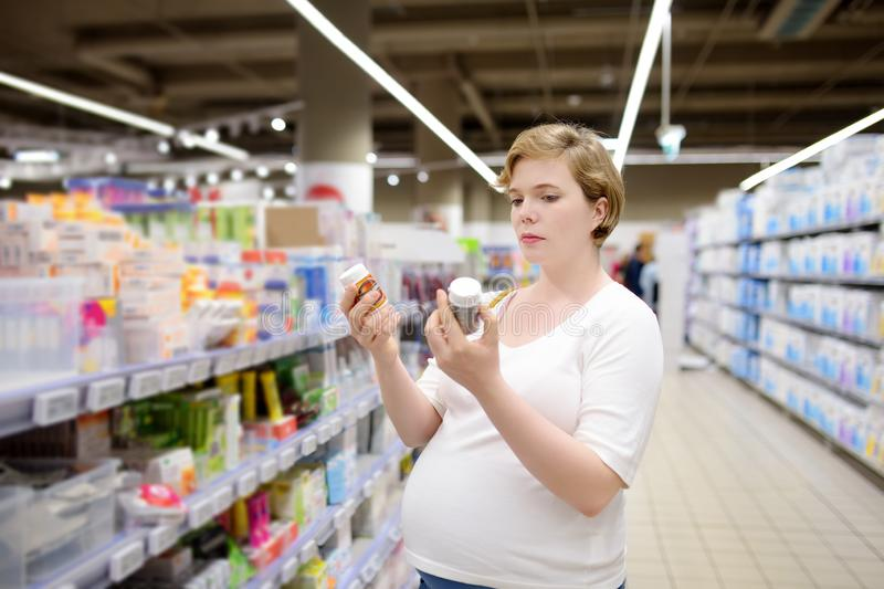Jonge zwangere vrouw die vitaminen, supplementen of schoonheidsmiddelen of zorgproducten in de opslag of de apotheek kiezen stock afbeelding