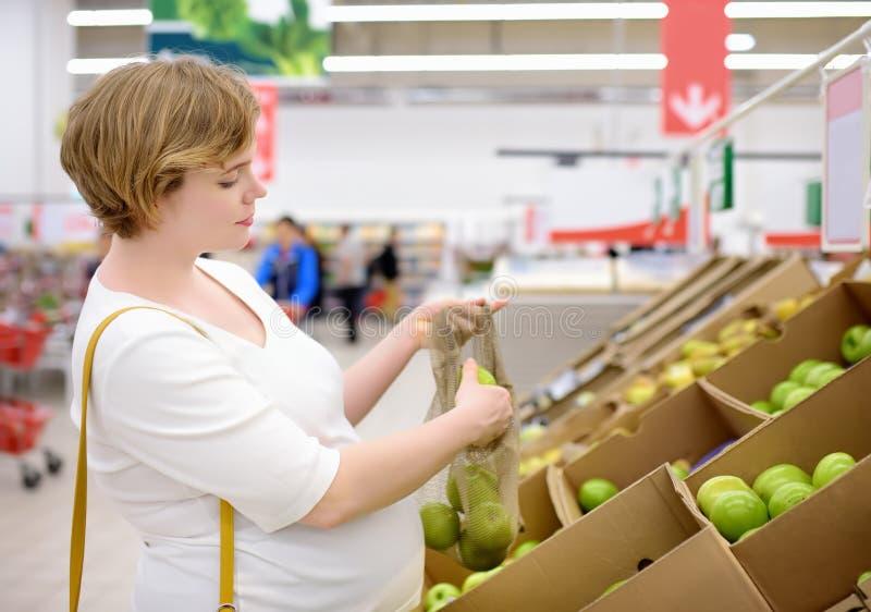 Jonge zwangere vrouw die vruchten en groenten in netwerk het winkelen zak in supermarkt kiezen stock afbeeldingen