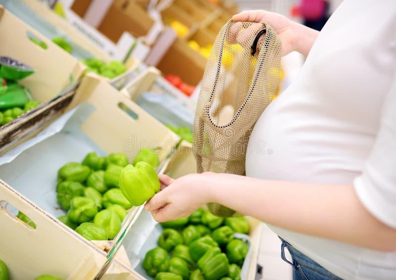Jonge zwangere vrouw die vruchten en groenten in netwerk het winkelen zak in supermarkt kiezen royalty-vrije stock afbeelding