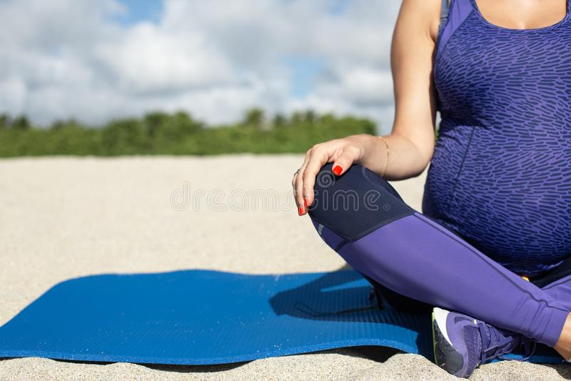 Jonge zwangere vrouw die yoga doet stock foto