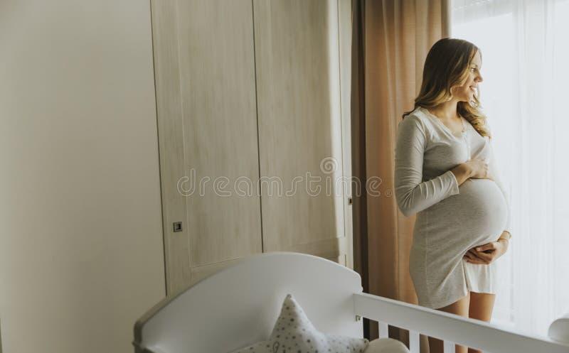 Jonge zwangere vrouw door de wieg in de ruimte royalty-vrije stock afbeeldingen