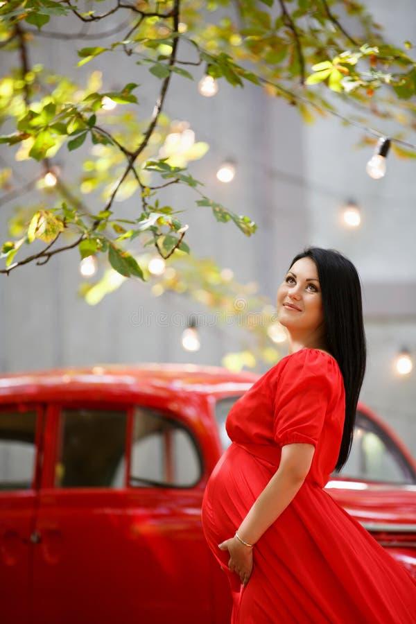 Jonge zwangere vrouw in een de herfsttuin stock foto