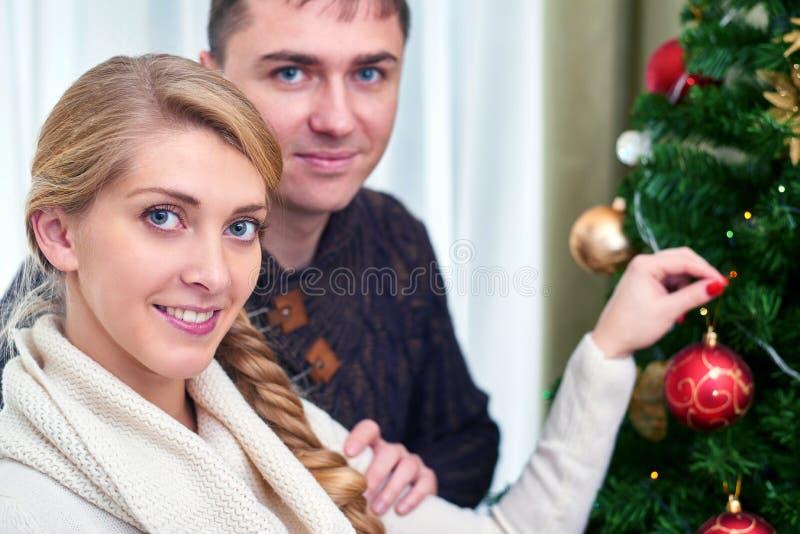 Jonge zwangere vrouw en gelukkige vader die Kerstboom verfraaien stock afbeeldingen
