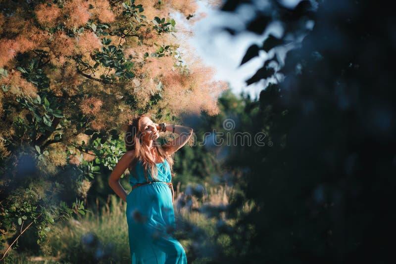 Jonge zwangere vrouw in het park in openlucht Kalme zwangere vrouw in derde trimester Het lopen in openbare tuin stock foto