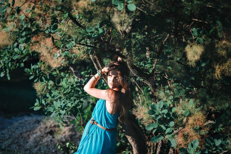 Jonge zwangere vrouw in het park in openlucht Kalme zwangere vrouw in derde trimester Het lopen in openbare tuin stock afbeelding
