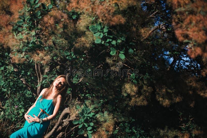 Jonge zwangere vrouw in het park in openlucht Kalme zwangere vrouw in derde trimester Het lopen in openbare tuin stock fotografie