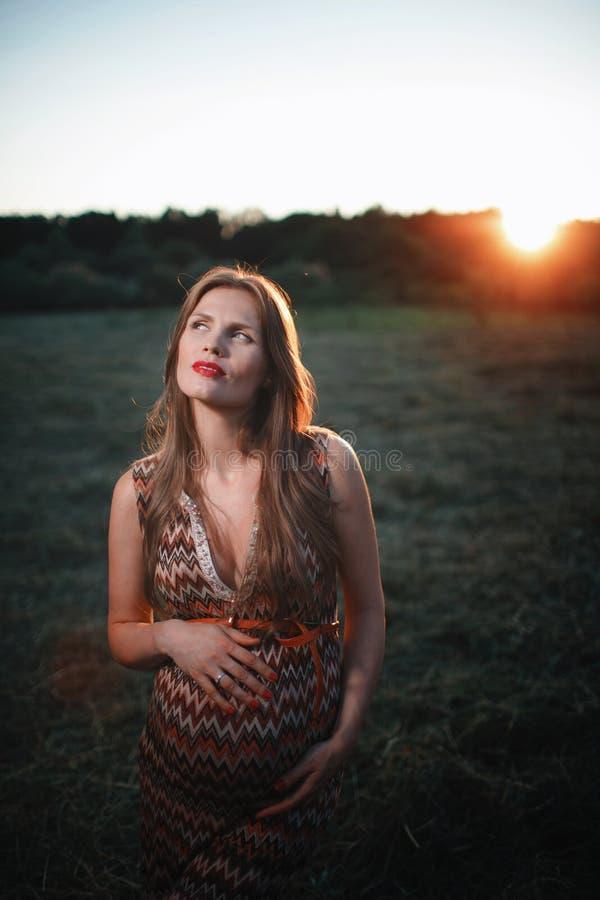 Jonge zwangere vrouw in het park in openlucht Kalme zwangere vrouw in derde trimester Het lopen in openbare tuin Zonsondergang bi stock foto's