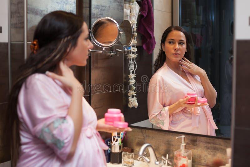 Jonge zwangere vrouw met kosmetische room. royalty-vrije stock foto