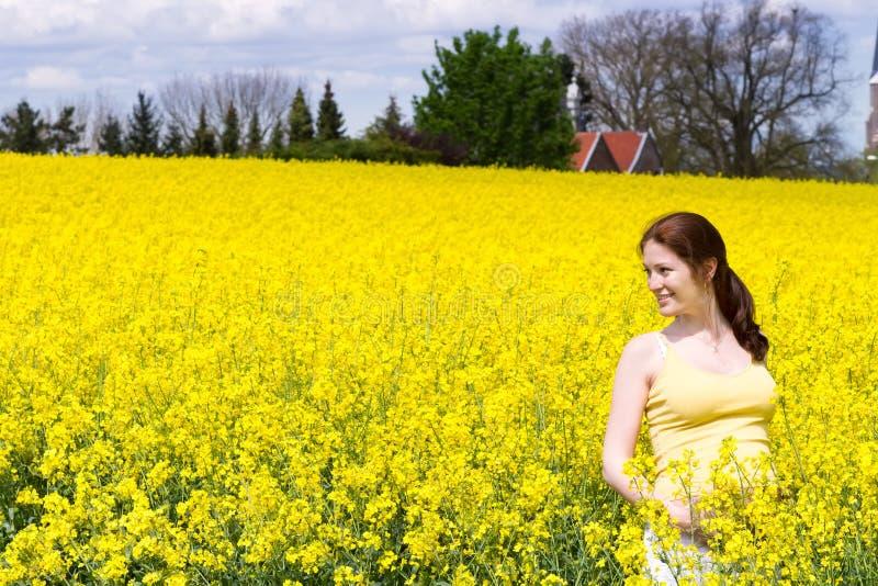 Jonge zwangere vrouw op geel bloemgebied royalty-vrije stock foto