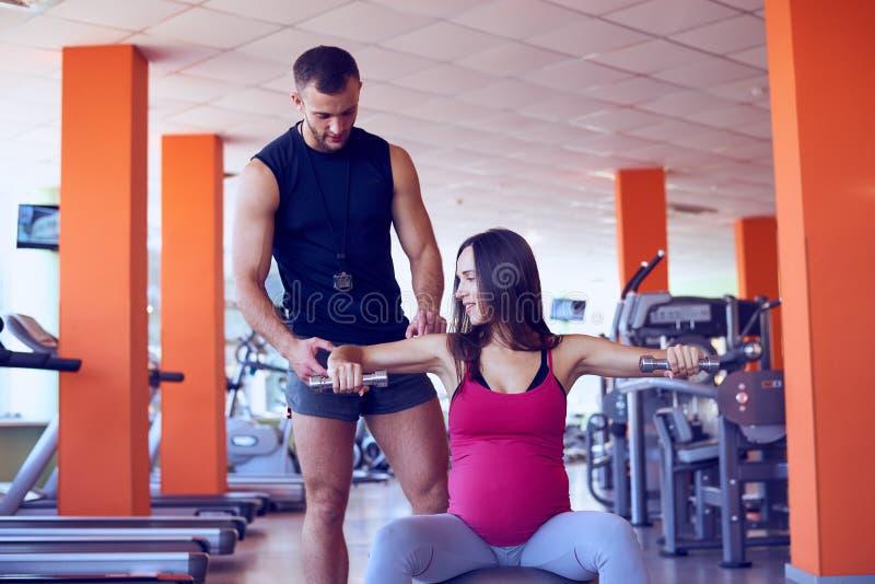 Jonge zwangere vrouwen opheffende domoren op fitball stock fotografie