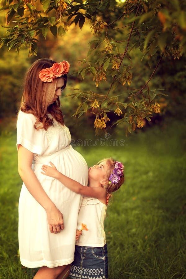 Jonge zwangere vrouwengangen met haar dochter Meisje hun koesteren royalty-vrije stock afbeeldingen