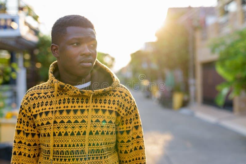 Jonge zwarte Afrikaanse mens die terwijl het kijken aan de kant en w denken royalty-vrije stock afbeeldingen