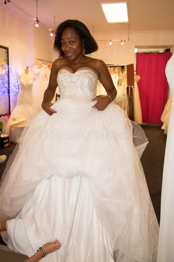 Jonge zwarte Afrikaanse vrouwenmontage gekleed in luxe witte toga die zich in de kledingssalon van de huwelijkswinkel bevinden stock afbeeldingen