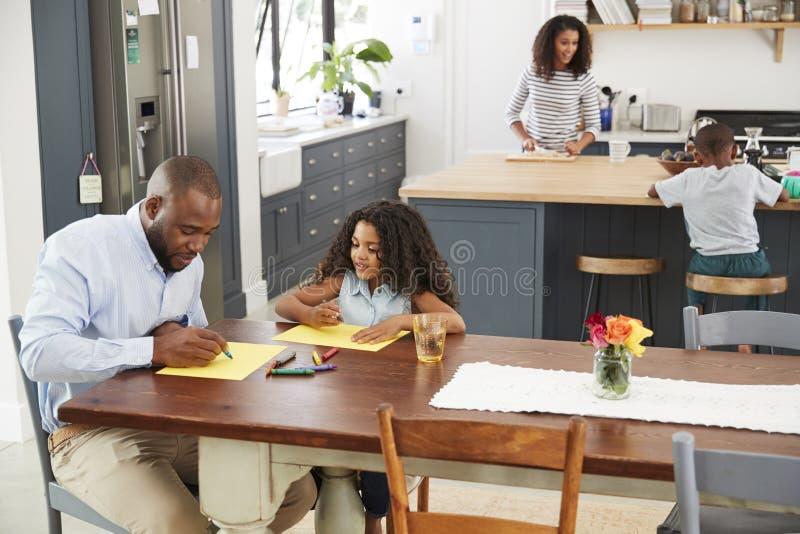 Jonge zwarte familie bezig in hun keuken, opgeheven mening royalty-vrije stock foto