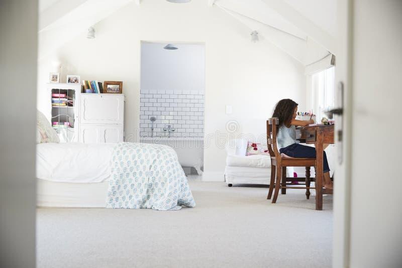 Jonge zwarte meisjeszitting bij bureau, die thuiswerk in haar ruimte doen royalty-vrije stock afbeeldingen