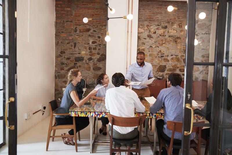 Jonge zwarte mens die administratie uitdelen op een teamvergadering stock afbeelding