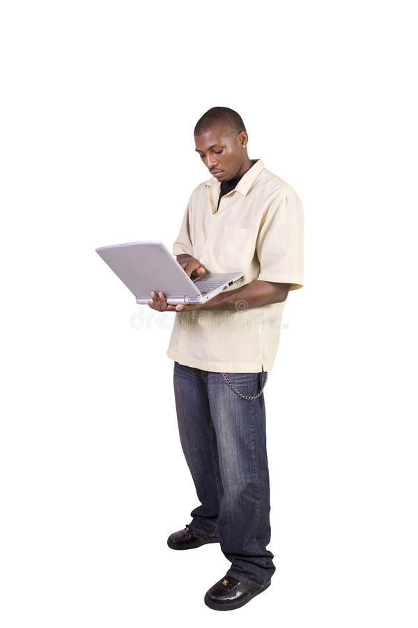 Jonge zwarte mens die en zich aan laptop bevindt werkt royalty-vrije stock afbeelding
