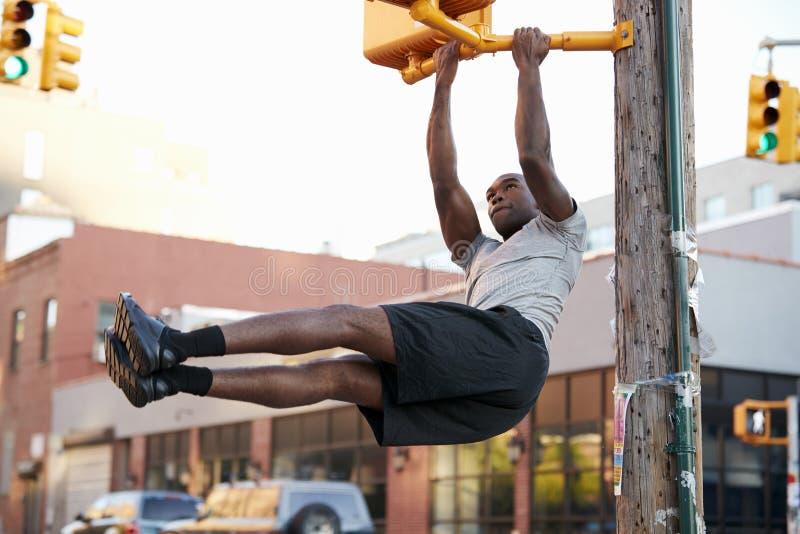 Jonge zwarte mens die trekkracht UPS van de kruising van licht in straat doen royalty-vrije stock fotografie