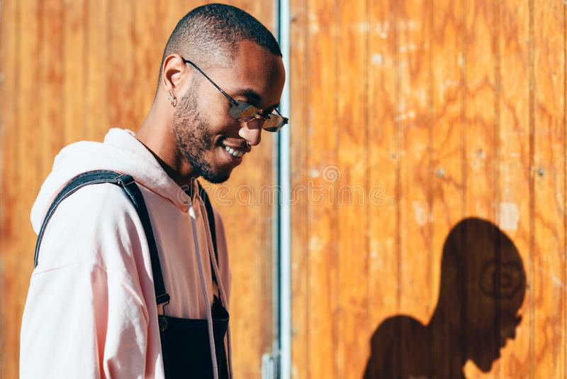 Jonge zwarte mens die vrijetijdskleding en zonnebril in openlucht dragen stock fotografie