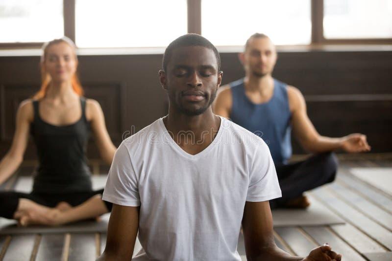 Jonge zwarte mens en groep mensen in Gemakkelijk Seat stock afbeeldingen