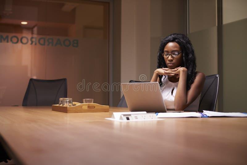 Jonge zwarte onderneemster die laat alleen in bureau werken stock afbeelding