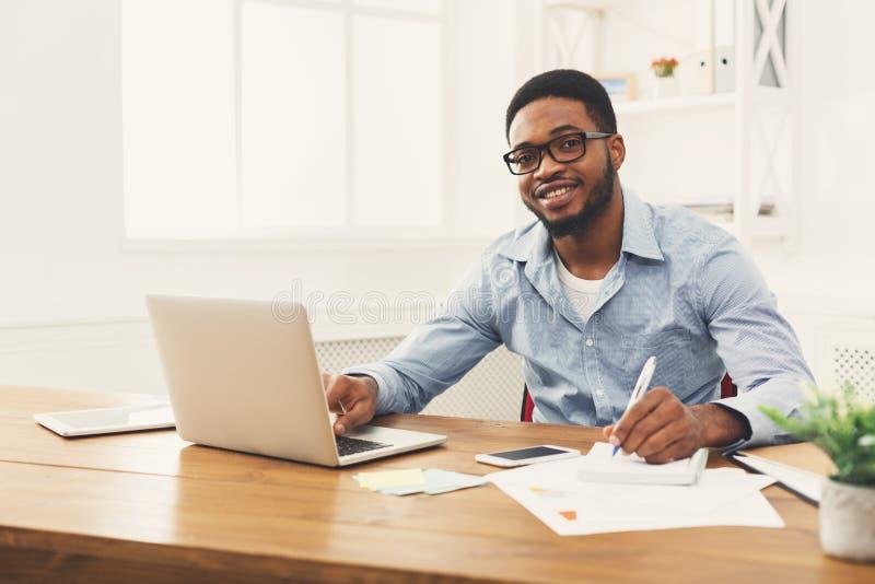 Jonge zwarte zakenman die met laptop werken royalty-vrije stock fotografie
