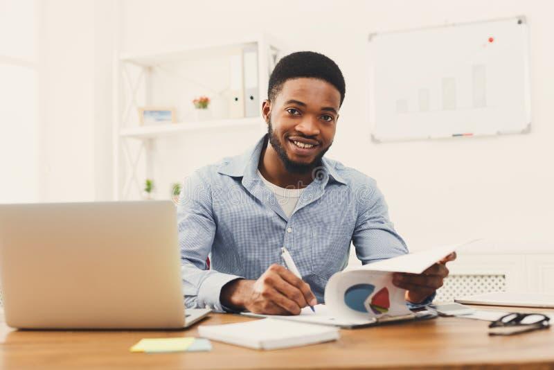 Jonge zwarte zakenman die met laptop werken stock foto's