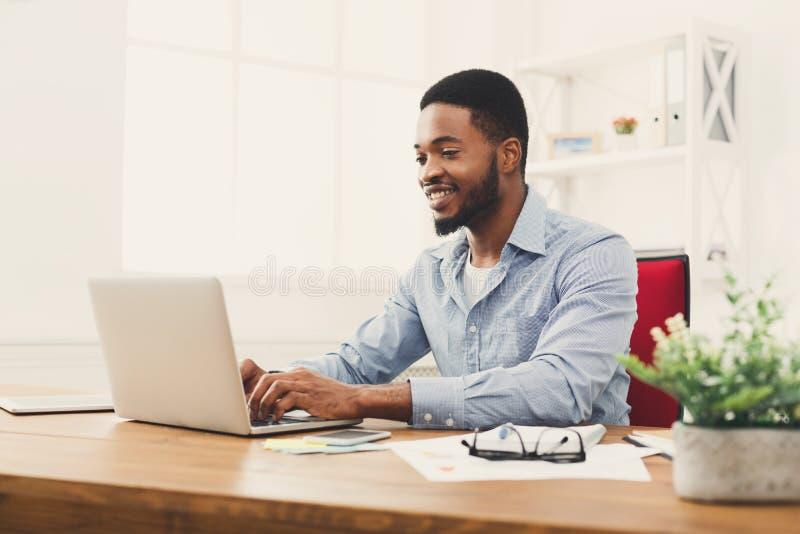 Jonge zwarte zakenman die met laptop werken royalty-vrije stock foto