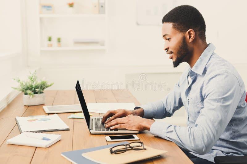 Jonge zwarte zakenman die met laptop werken royalty-vrije stock afbeeldingen