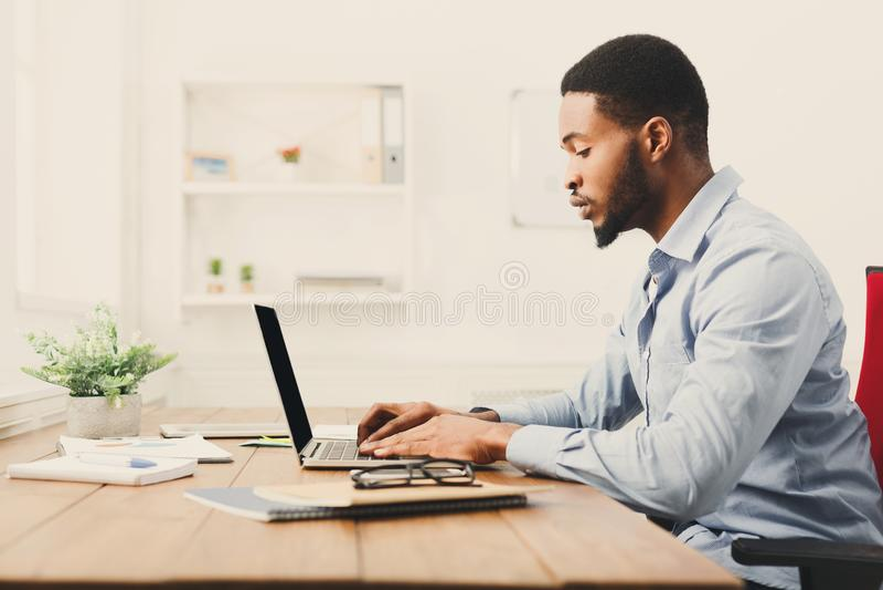 Jonge zwarte zakenman die met laptop werken stock afbeeldingen