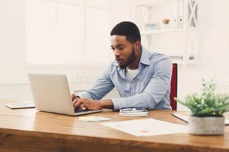 Jonge zwarte zakenman die met laptop werken royalty-vrije stock foto's