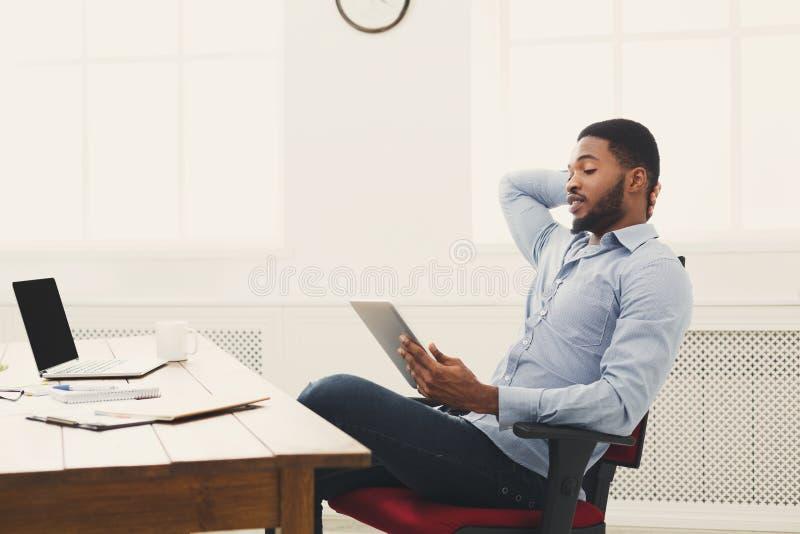 Jonge zwarte zakenman die met tablet werken royalty-vrije stock afbeeldingen