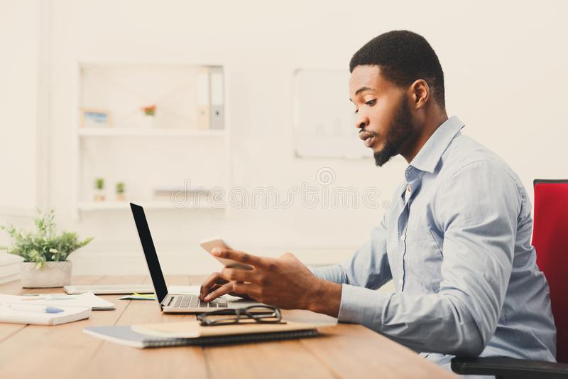 Jonge zwarte zakenman die mobiele telefoon met behulp van royalty-vrije stock afbeeldingen