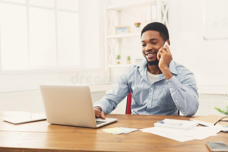 Jonge zwarte zakenman die op mobiele telefoon spreken stock foto