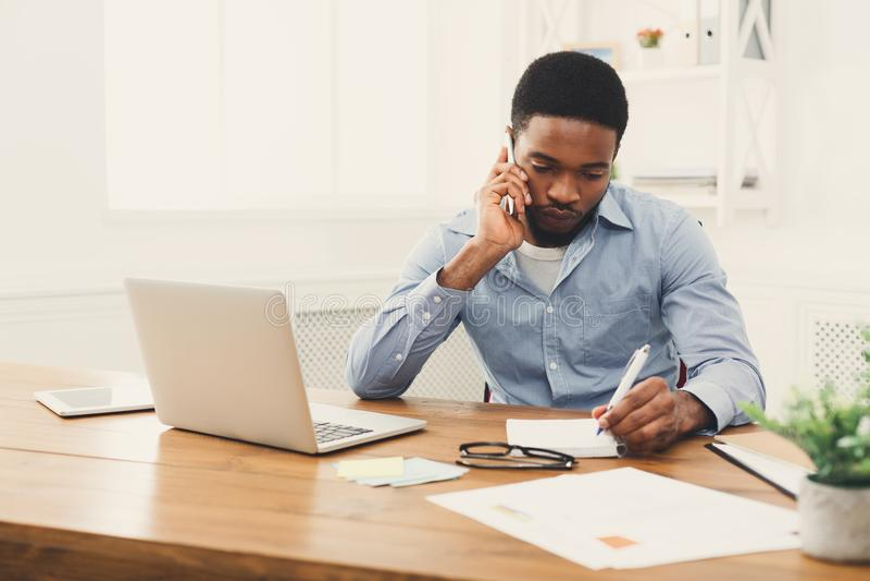 Jonge zwarte zakenman die op mobiele telefoon spreken royalty-vrije stock afbeelding