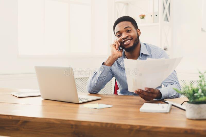 Jonge zwarte zakenman die op mobiele telefoon spreken stock fotografie