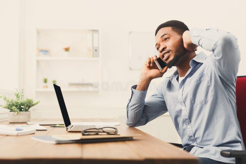 Jonge zwarte zakenman die op mobiele telefoon spreken royalty-vrije stock afbeeldingen