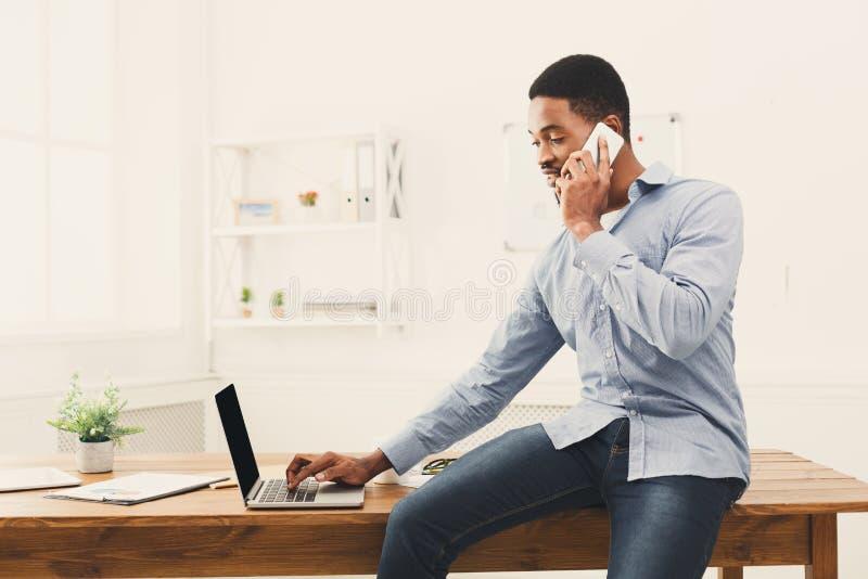 Jonge zwarte zakenman die telefoonbespreking hebben royalty-vrije stock foto's