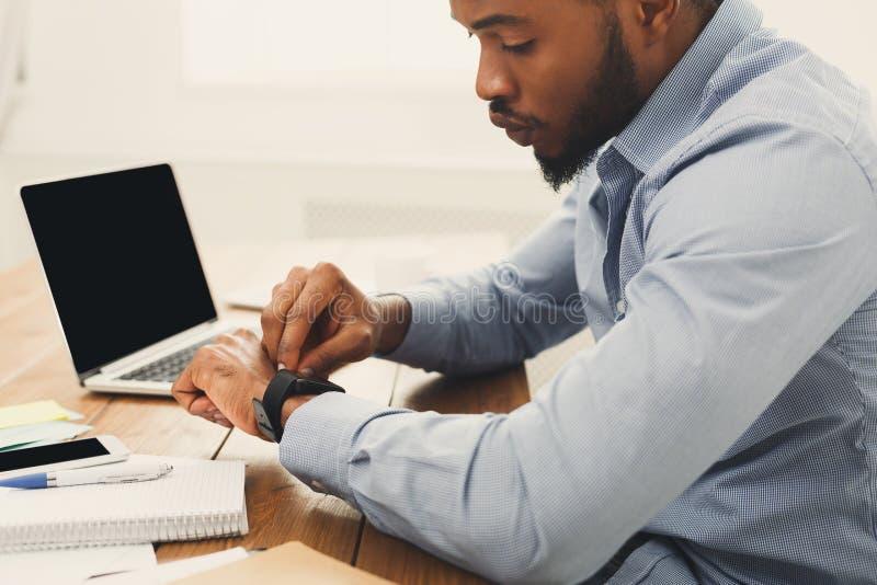 Jonge zwarte zakenman met smartwatch in bureau royalty-vrije stock afbeelding