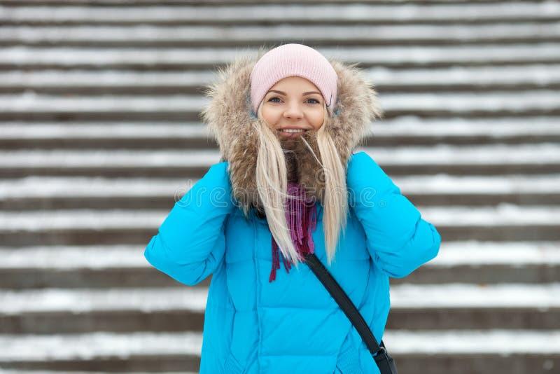 Jongelui die aanbiddelijke blonde vrouw glimlachen die blauwe laag dragen die met een kap in het sneeuwpark van de de winterstad  royalty-vrije stock foto